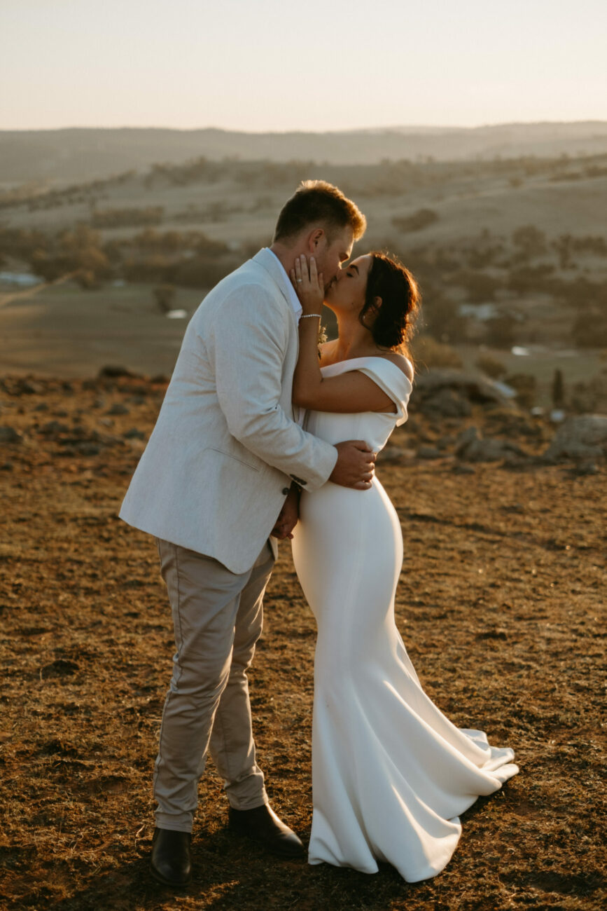 Bride and groom kissing up on top of a dry Australian outlook