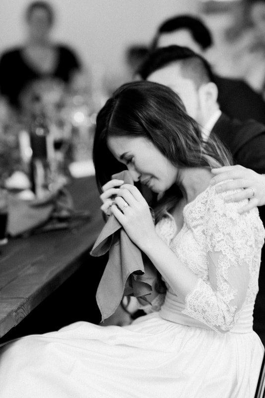 Bride crying while listening to reception speeches