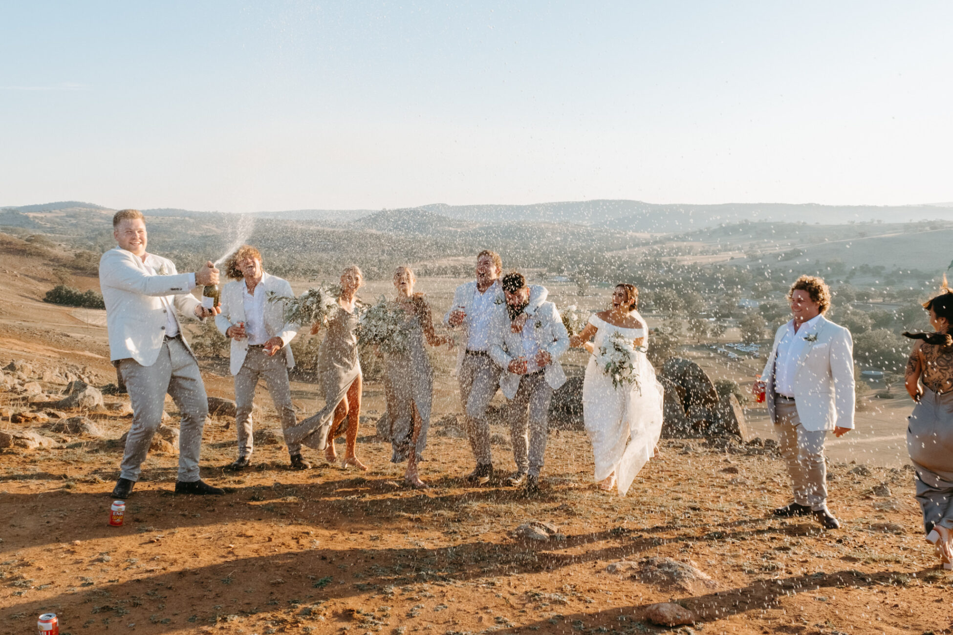 Champagne pop with bridal party, groom popping it and spraying bridal party